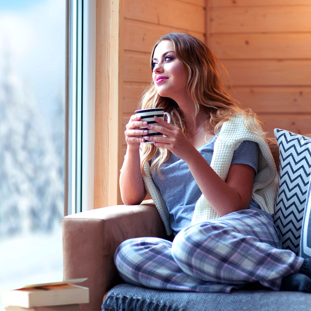 Girl drinking hot drink while watching outside